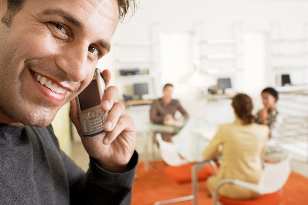 Stock Photo: 1654R-5744 Businessman using mobile phone in office portrait