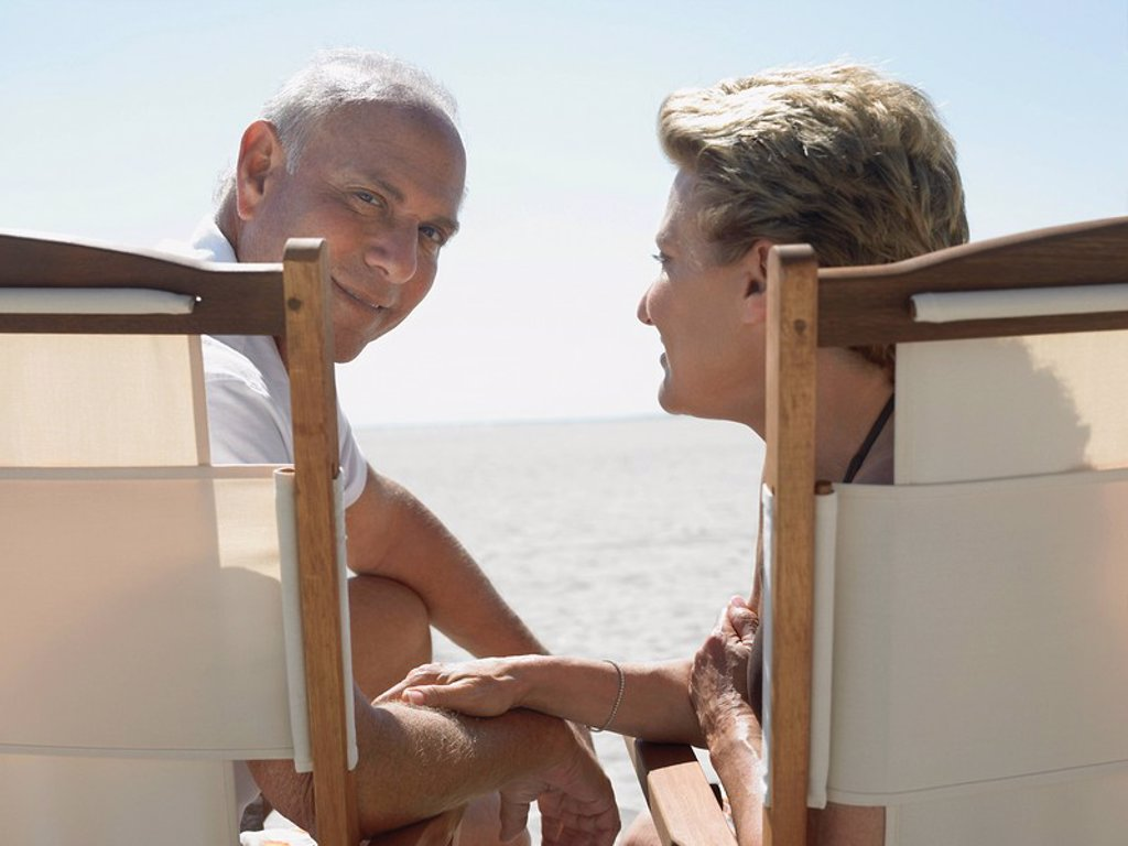 Senior couple on sunloungers on beach back view : Stock Photo
