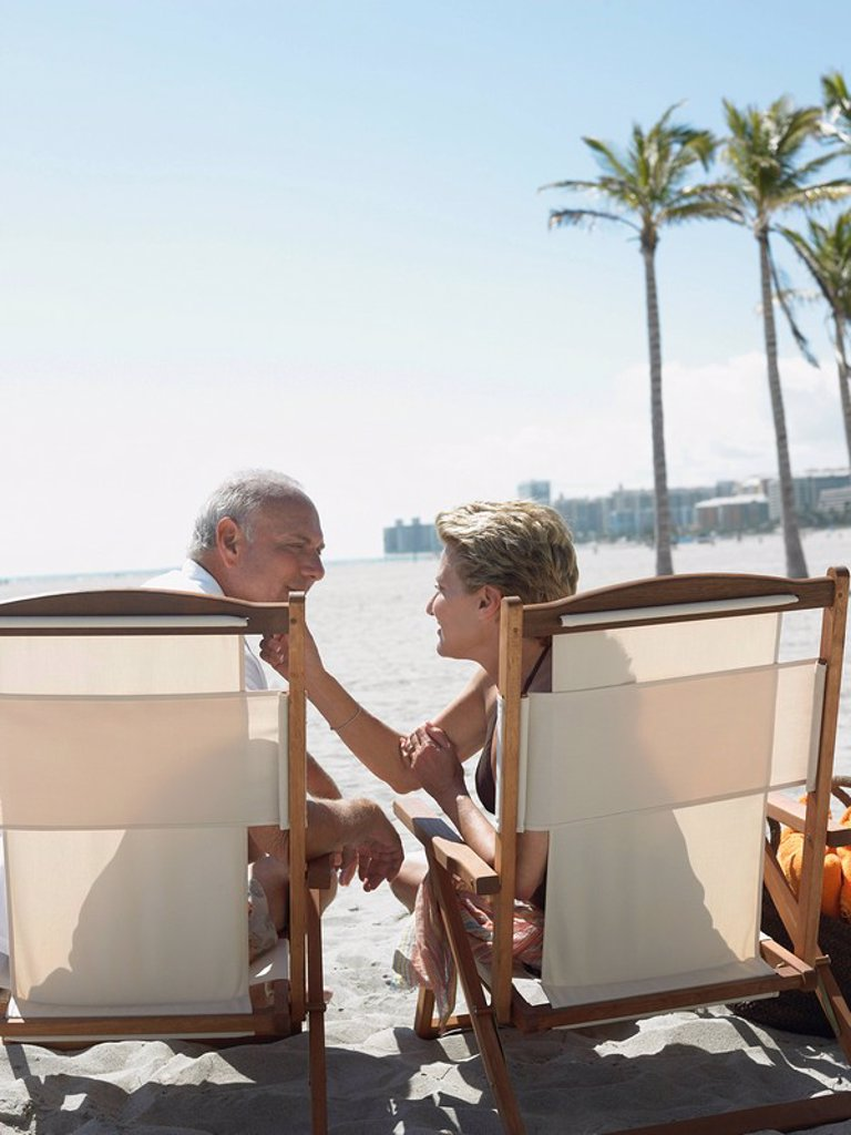 Senior couple on sunloungers on tropical beach back view : Stock Photo