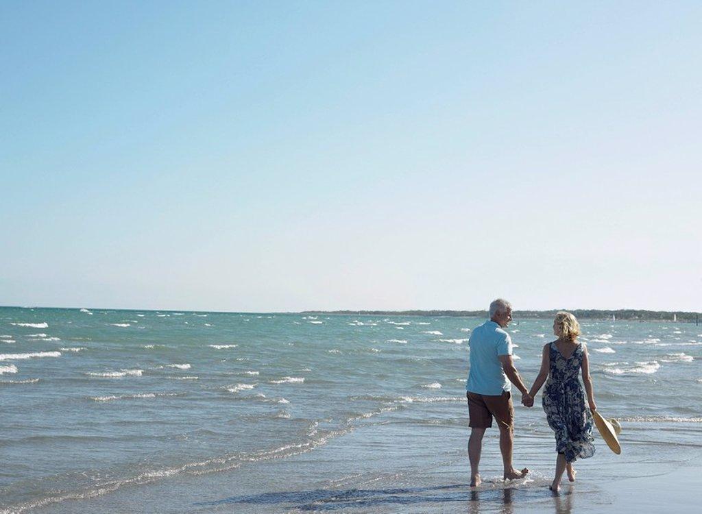 Stock Photo: 1654R-5780 Senior couple walking on beach back view