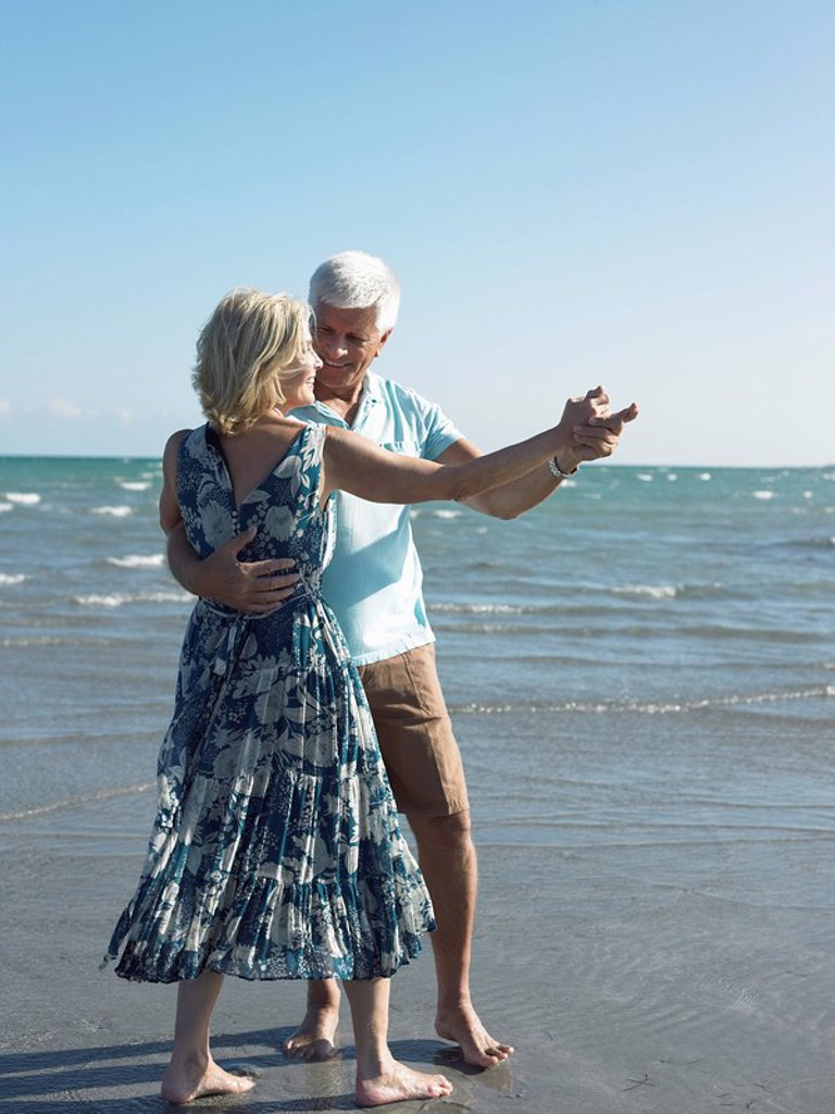 Stock Photo: 1654R-5784 Senior couple dancing on beach