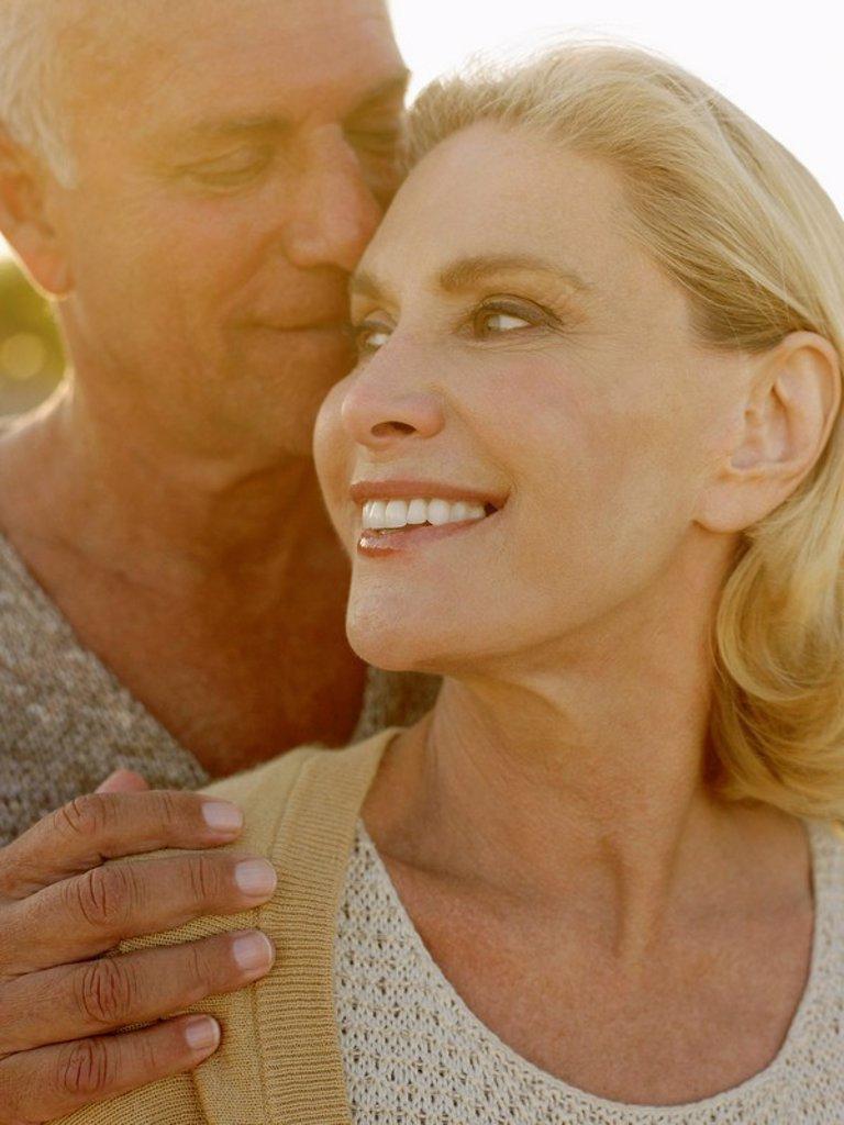Stock Photo: 1654R-5789 Senior couple embracing at sunset close up