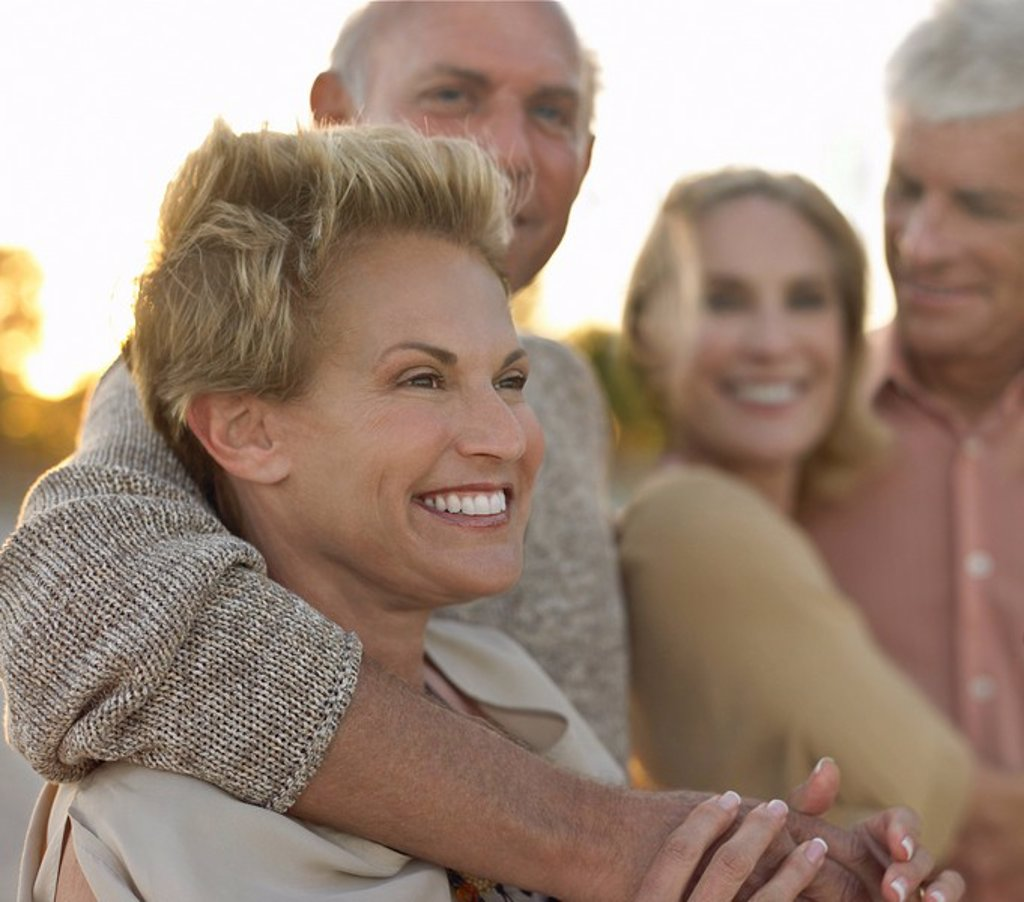 Senior couples relaxing together on beach : Stock Photo