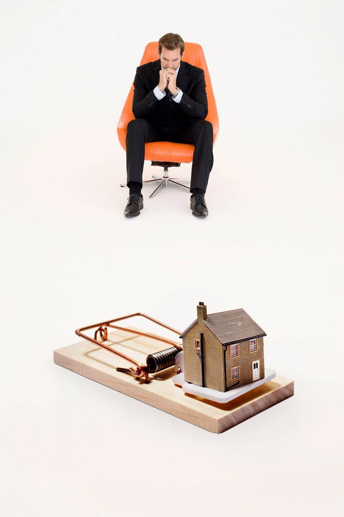 Model home on mouse trap with worried businessman sitting on chair representing increasing real estate rates : Stock Photo