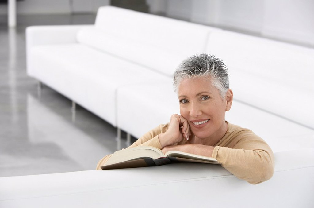 Stock Photo: 1654R-5806 Woman with book on sofa smiling portrait