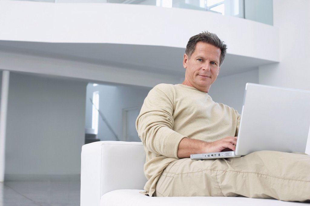 Man using laptop on sofa in living room portrait : Stock Photo