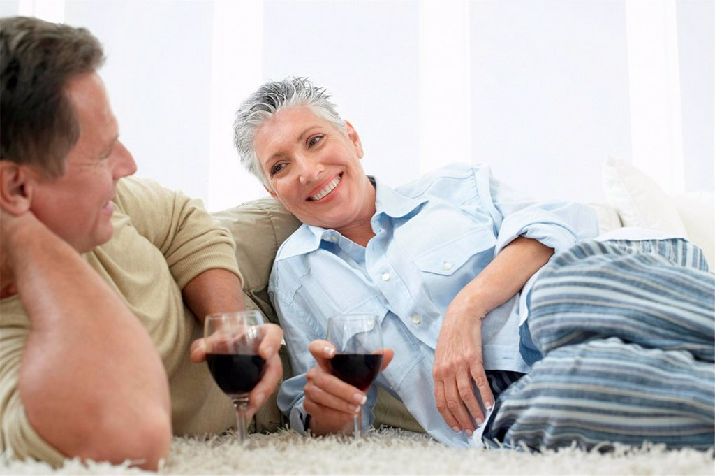 Couple drinking wine on rug in home : Stock Photo