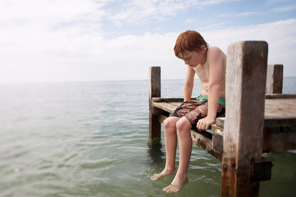 Pre_teen boy sitting on end of pier with feet in water portrait : Stock Photo