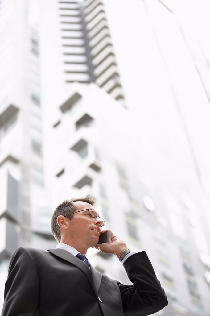 Businessman using mobile phone in front of tall building low angle view : Stock Photo