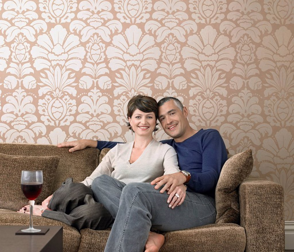 Stock Photo: 1654R-5944 Smiling couple relaxing on sofa in living room portrait