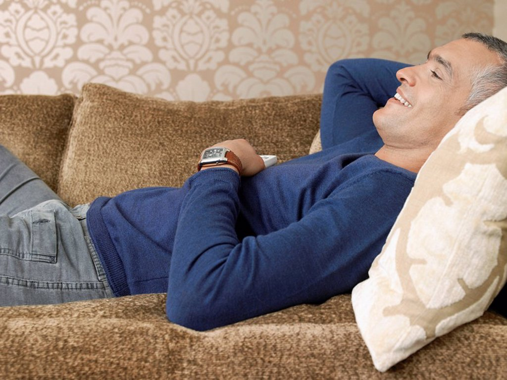 Smiling man laying on sofa : Stock Photo