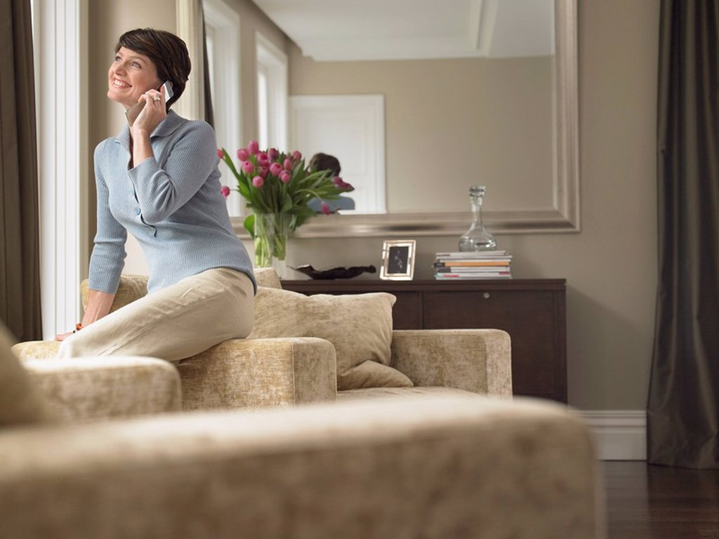 Smiling woman talking on mobile phone in living room : Stock Photo
