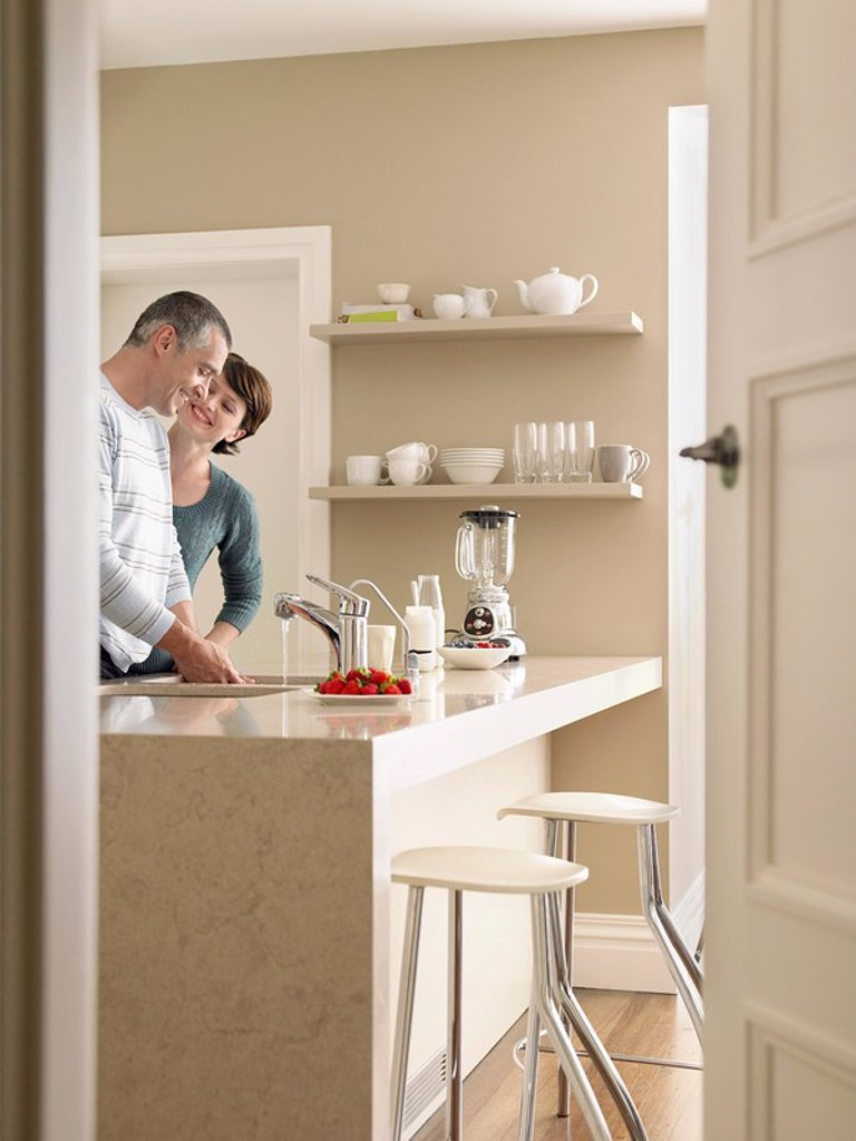 Smiling couple in kitchen seen through open door : Stock Photo