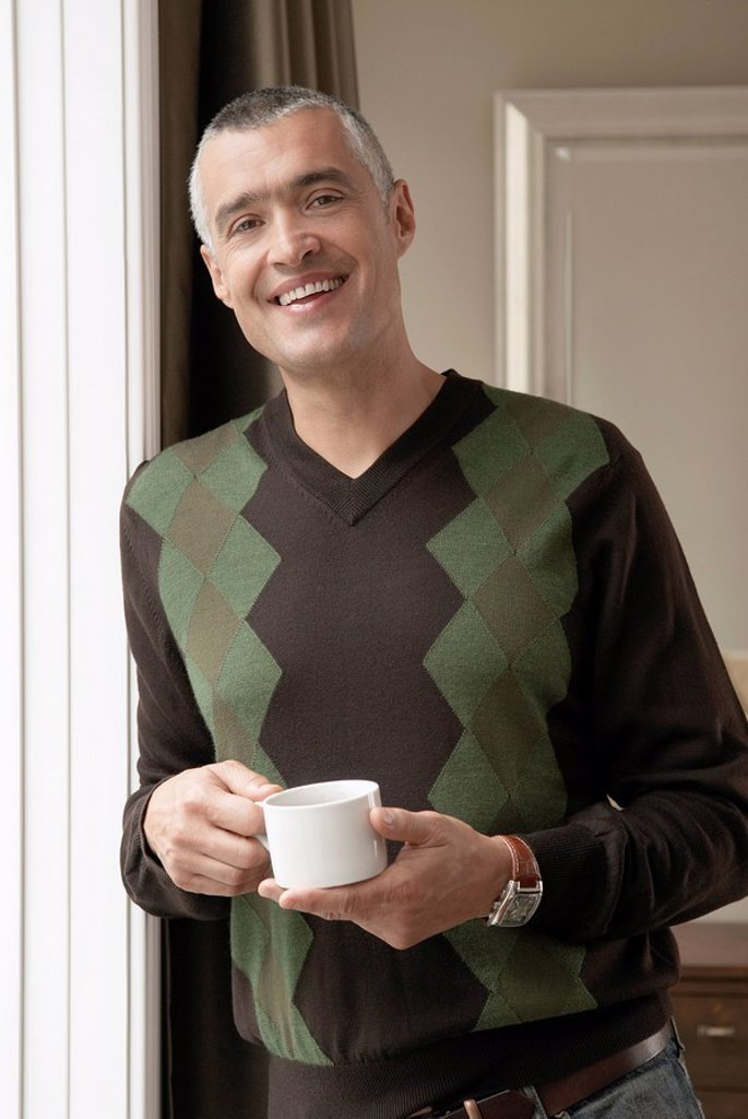 Stock Photo: 1654R-5962 Smiling man with cup of coffee portrait