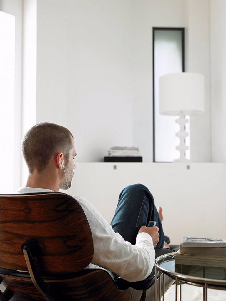 Man Sitting in Chair Listening to MP3 Player back view : Stock Photo