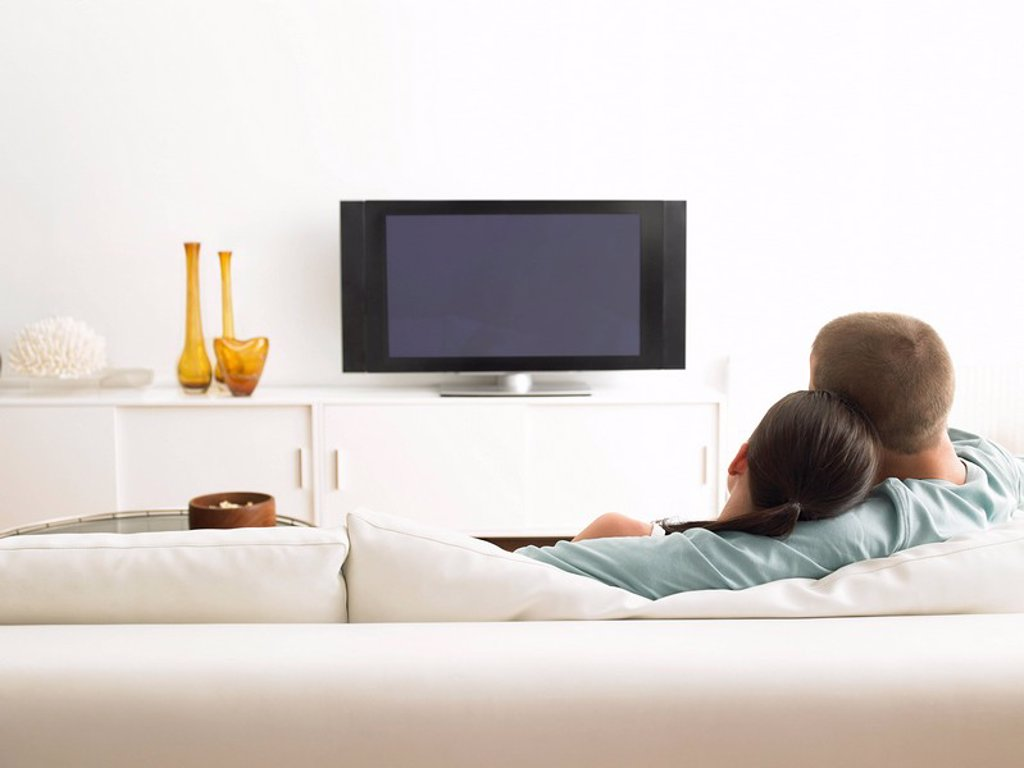 Rear View of couple on sofa watching TV : Stock Photo