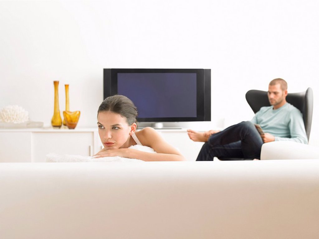 Woman on sofa and man in armchair in modern living room : Stock Photo