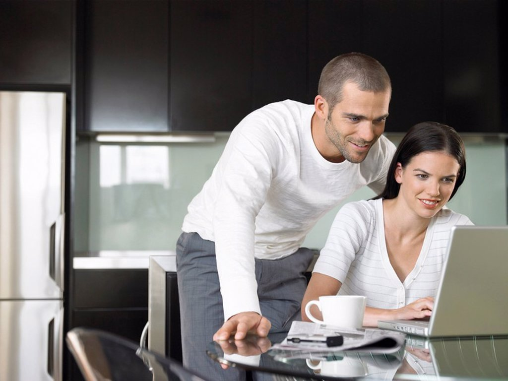 Couple looking at lap top in modern kitchen : Stock Photo