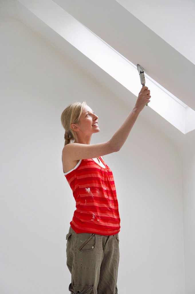 Woman painting sloping ceiling : Stock Photo