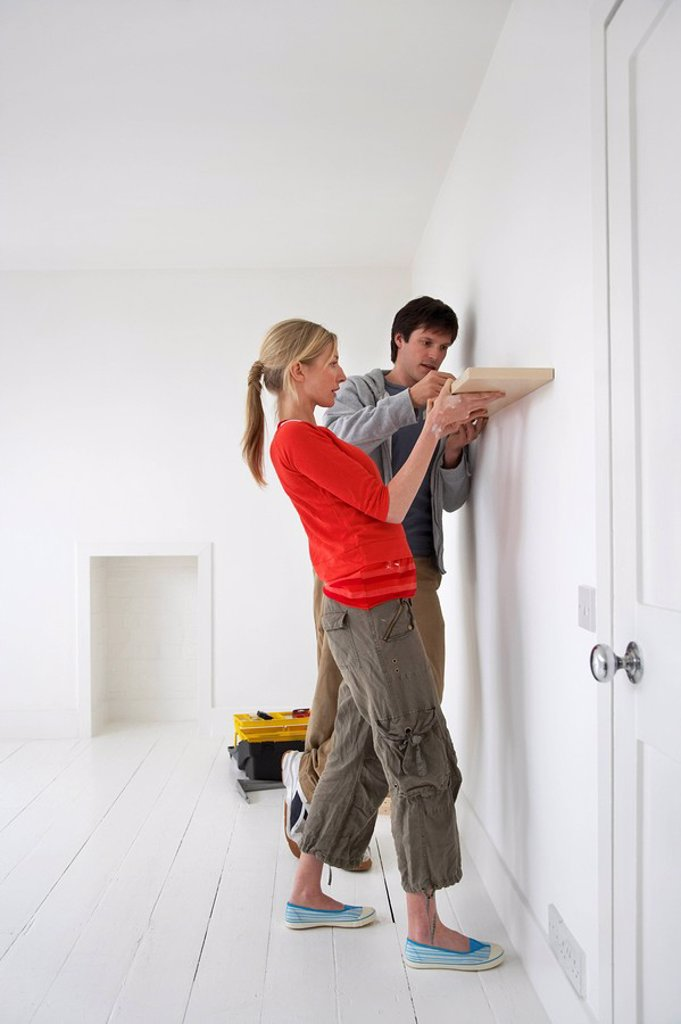 Stock Photo: 1654R-6042 Couple putting up shelf in new home