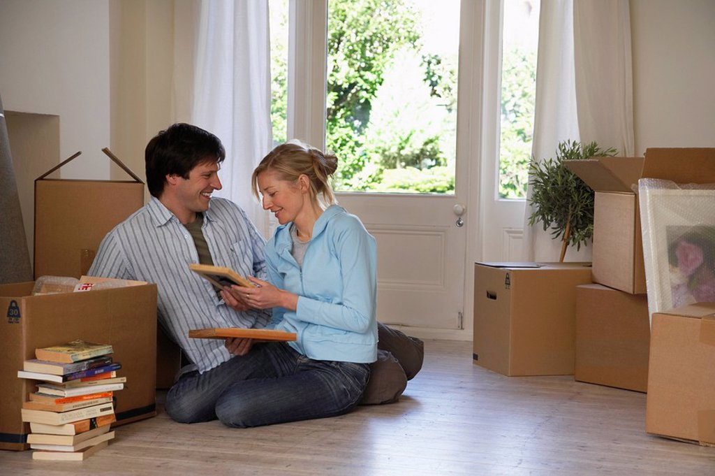 Stock Photo: 1654R-6058 Couple sitting on floor at home with boxes and books