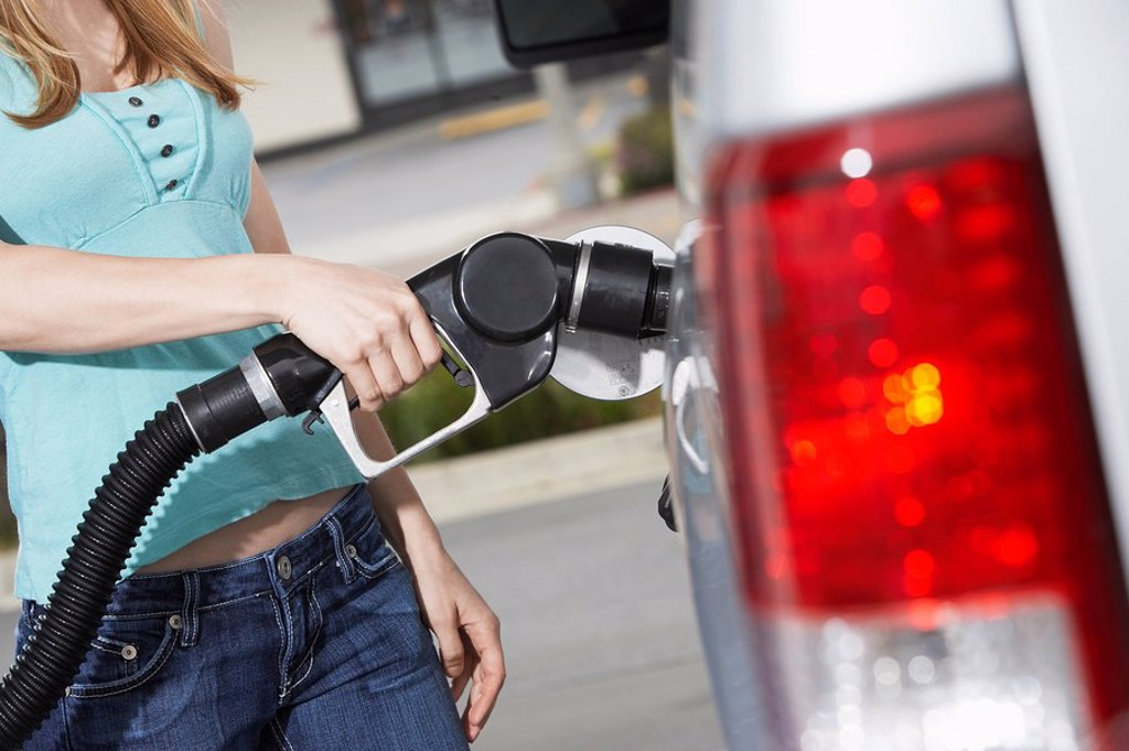 Young woman filling car with gas at gas station mid section : Stock Photo