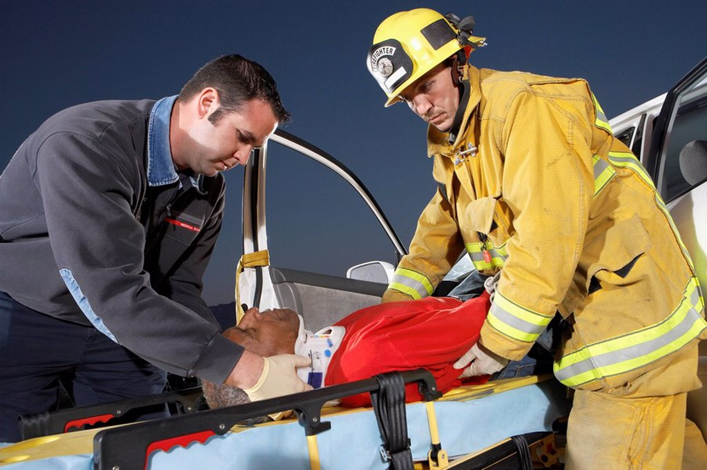 Fire fighter and paramedic assisting man at crash site : Stock Photo