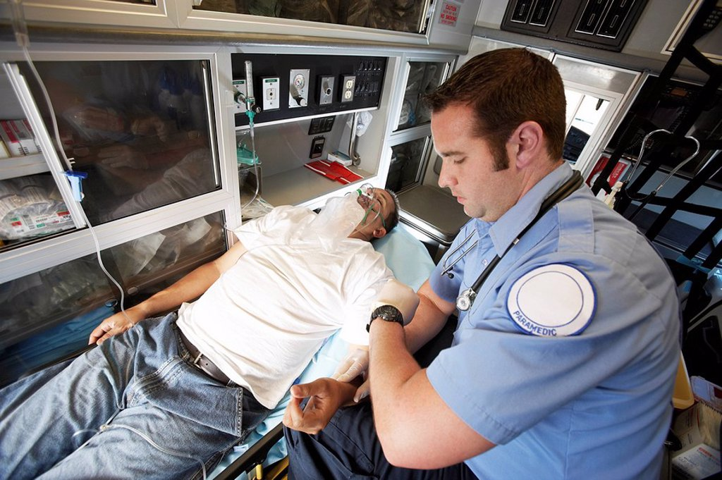 Man receiving medical aid inside ambulance : Stock Photo