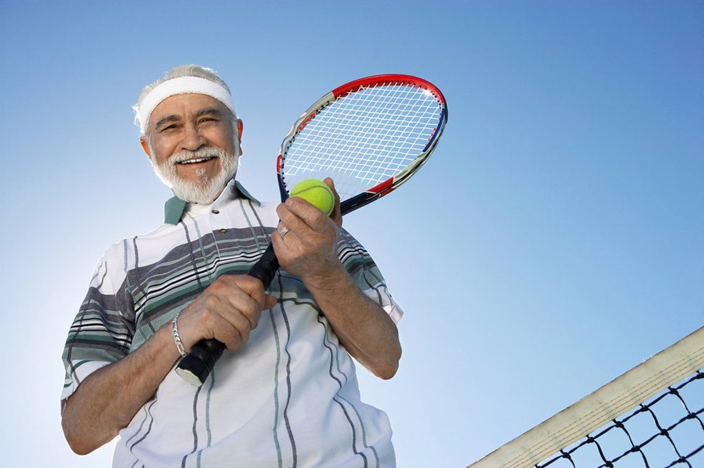 Smiling Man holding racket and ball standing above net low angle view : Stock Photo