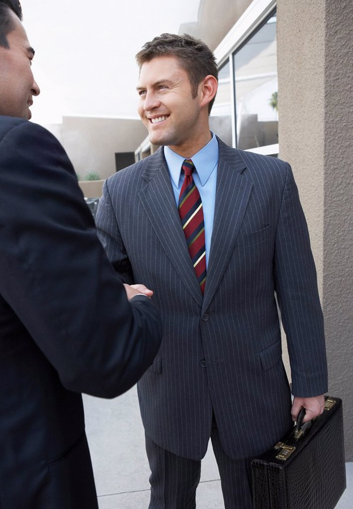 Stock Photo: 1654R-6401 Two Businessmen Shaking Hands outside office