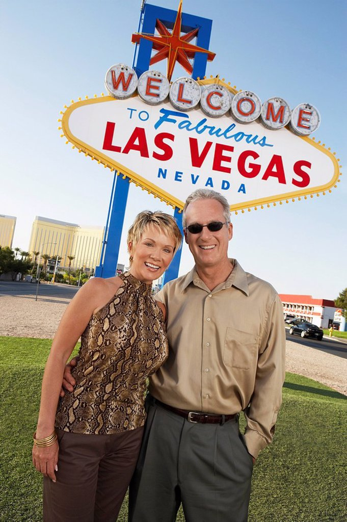 Stock Photo: 1654R-6554 Couple in front of Welcome to Las Vegas sign portrait