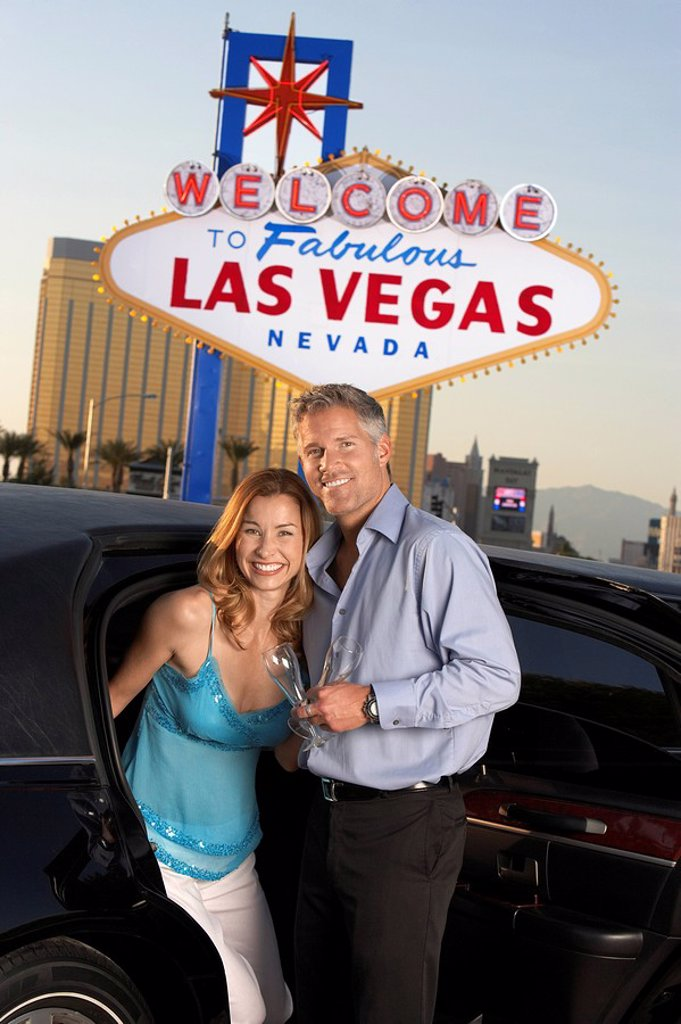 Stock Photo: 1654R-6556 Couple getting out of limousine man holding empty glass in front of Welcome to Las Vegas sign