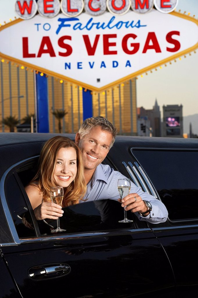 Couple sitting in limousine with drinking glasses in front of Welcome to Las Vegas sign : Stock Photo