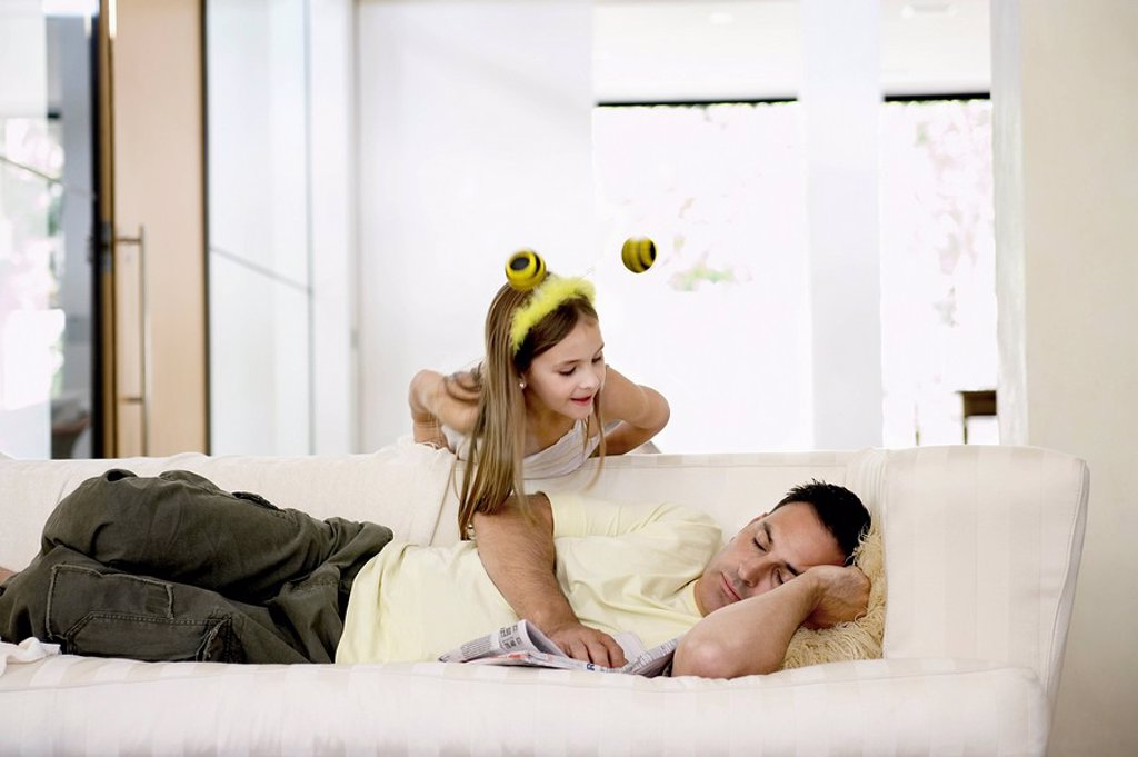 Man napping on sofa with daughter leaning over : Stock Photo