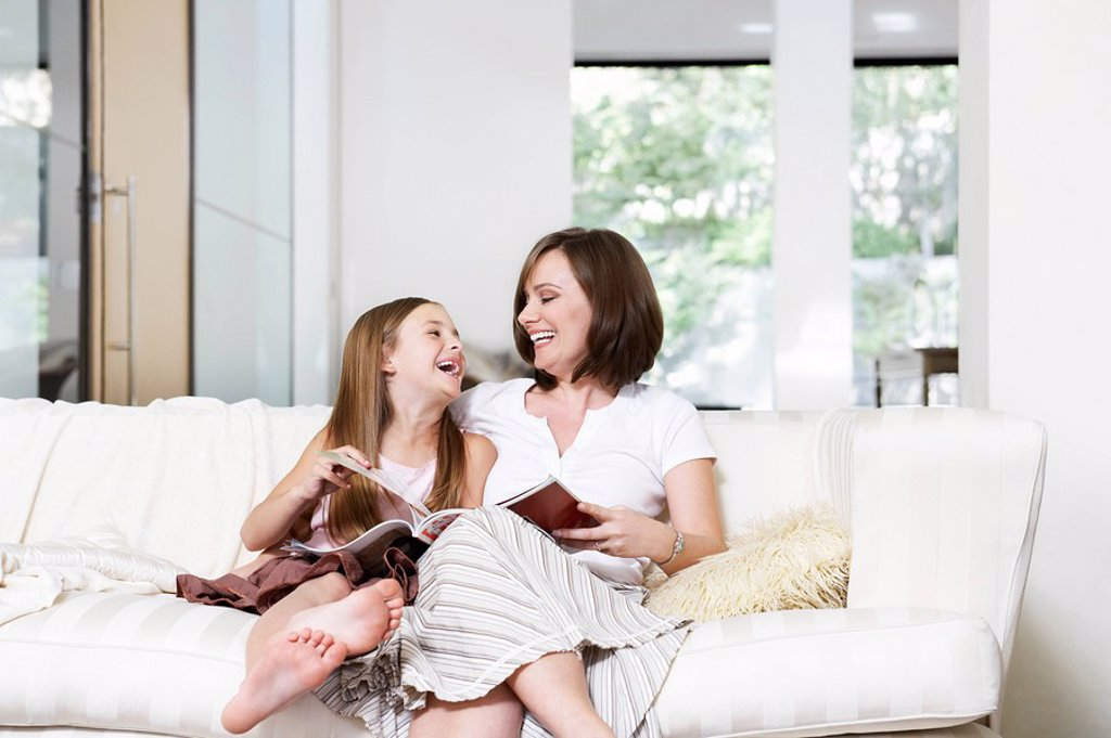 Stock Photo: 1654R-6592 Mother and daughter reading book in living room portrait