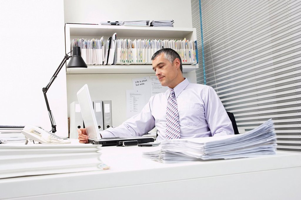 Businessman using laptop at office desk : Stock Photo