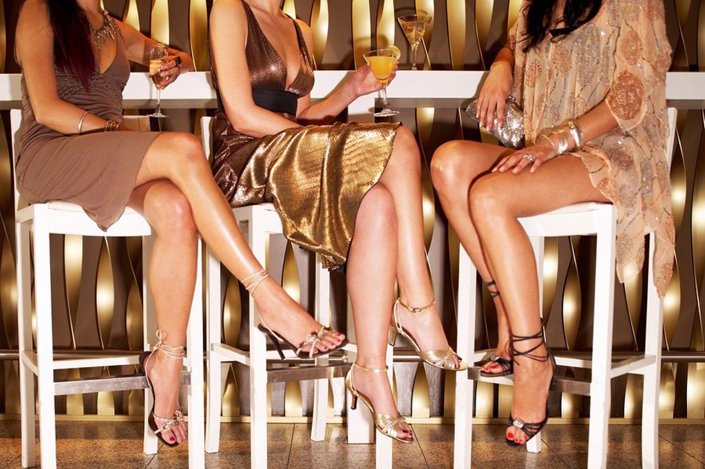Stylishly dressed women sitting legs crossed at bar drinking low section : Stock Photo
