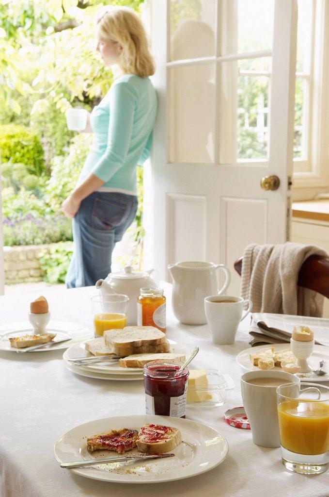Woman With Tea standing in doorway hand on hip After Breakfast : Stock Photo