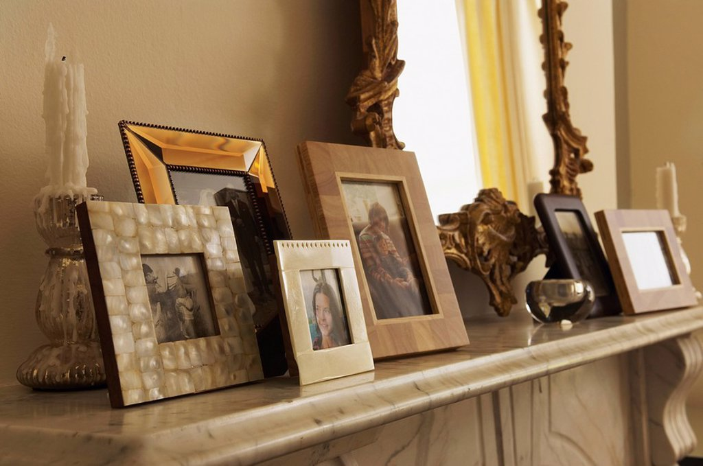 Stock Photo: 1654R-6747 Marble Fireplace Mantel With Framed Pictures and mirror