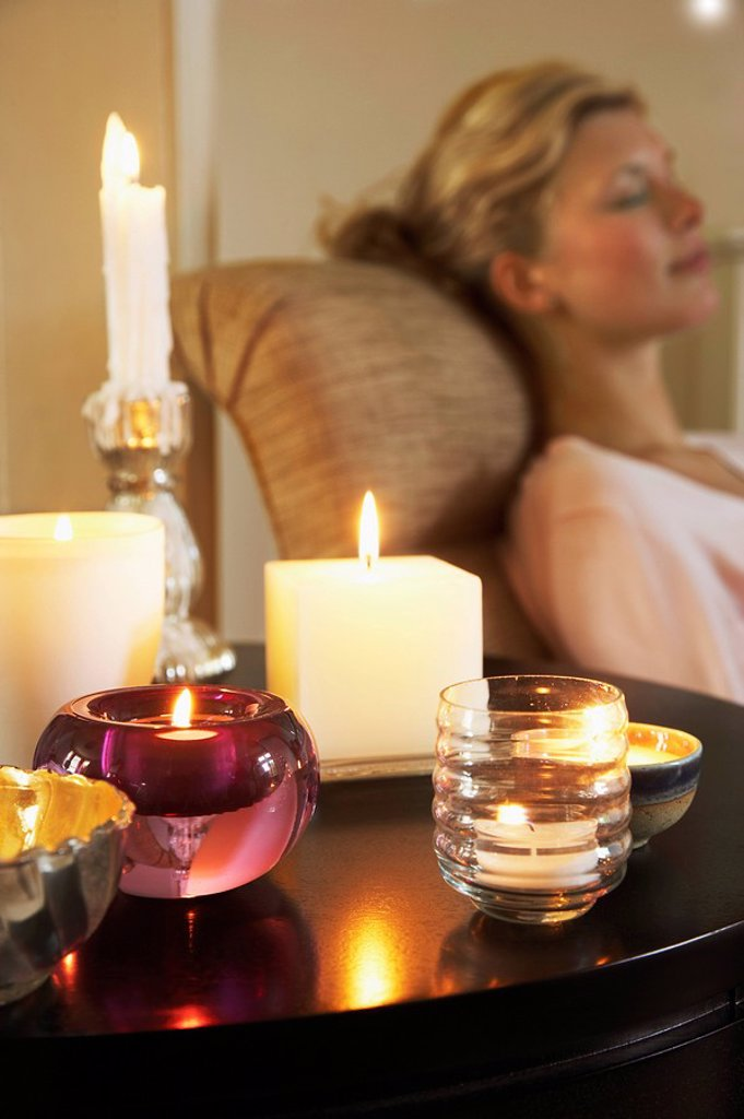 Stock Photo: 1654R-6759 Woman Relaxing on sofa beside table with Candles