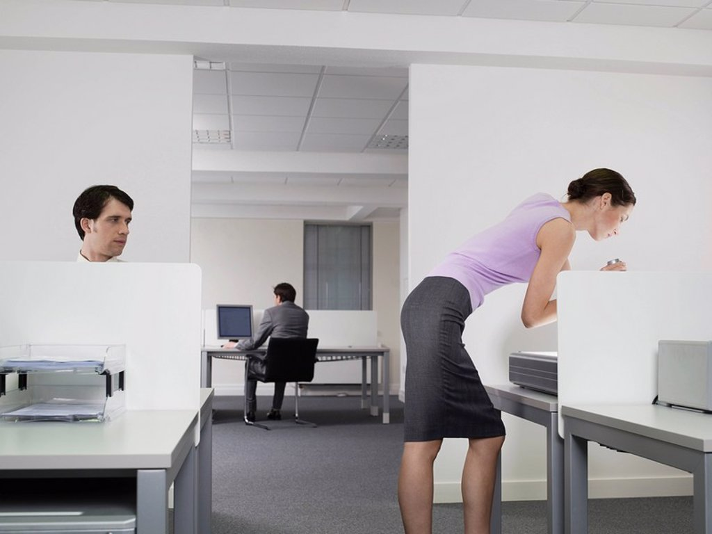 Businessman watching female colleague in office : Stock Photo