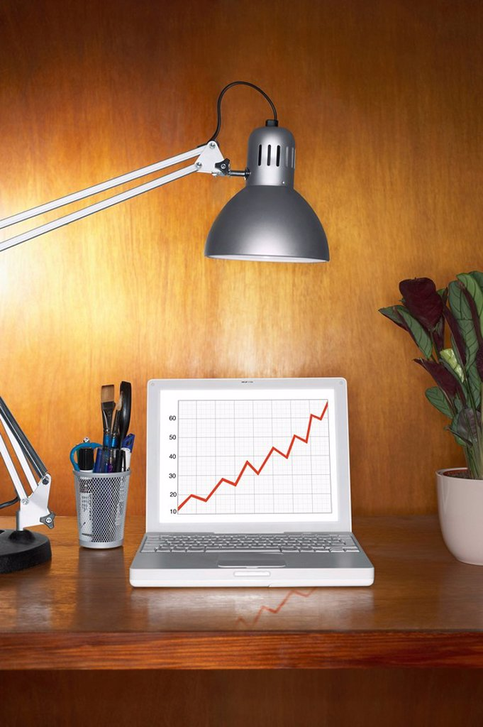 Laptop showing graph and other items on desk : Stock Photo