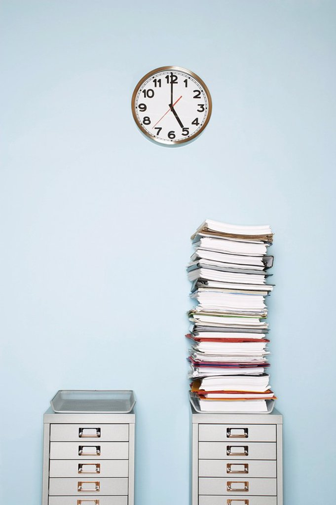 Stock Photo: 1654R-6921 Office wall with clock stack of paperwork in outbox on file cabinet