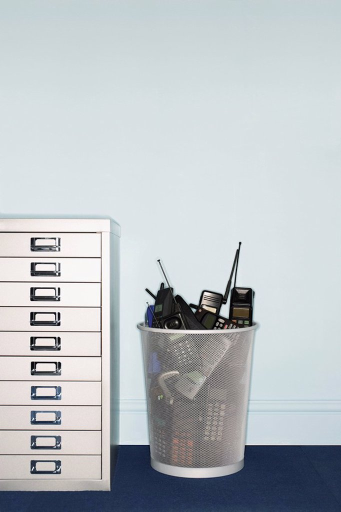 Mobile phones in trash can by filing cabinet : Stock Photo