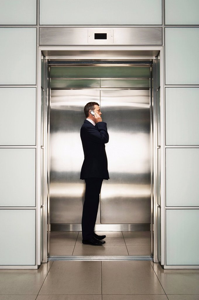 Stock Photo: 1654R-6990 Businessman Using Cell Phone in Elevator side view