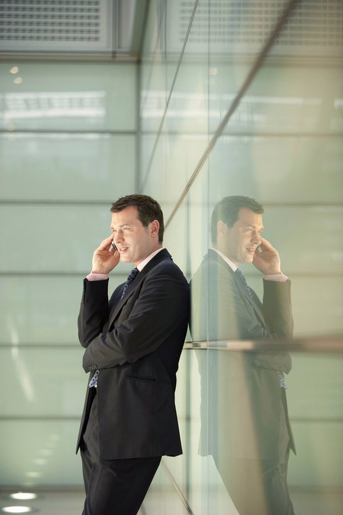 Businessman Using Cell Phone in Office Corridor : Stock Photo