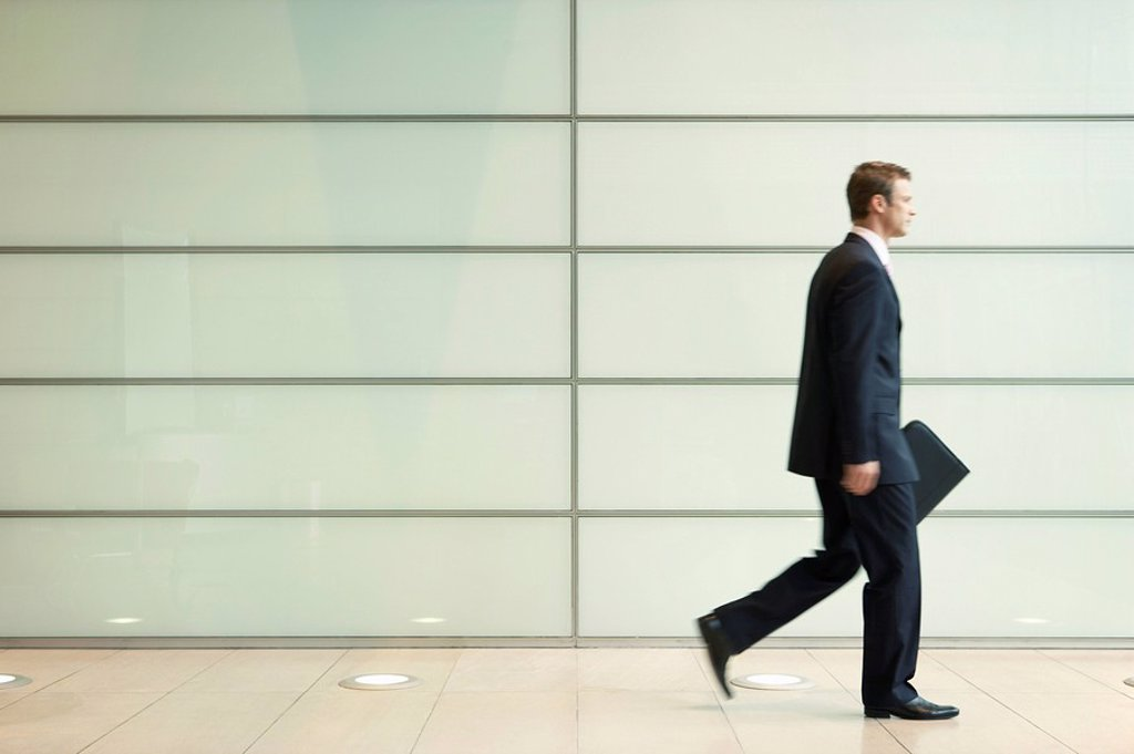 Businessman Striding Down Office Corridor side view : Stock Photo