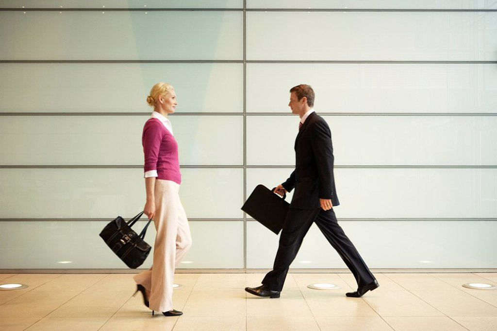 Businesspeople Walking in Office Hallway side view : Stock Photo