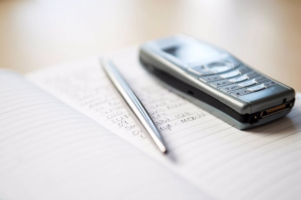 Stock Photo: 1654R-7055 Still life of mobile phone and silver pen resting on notebook