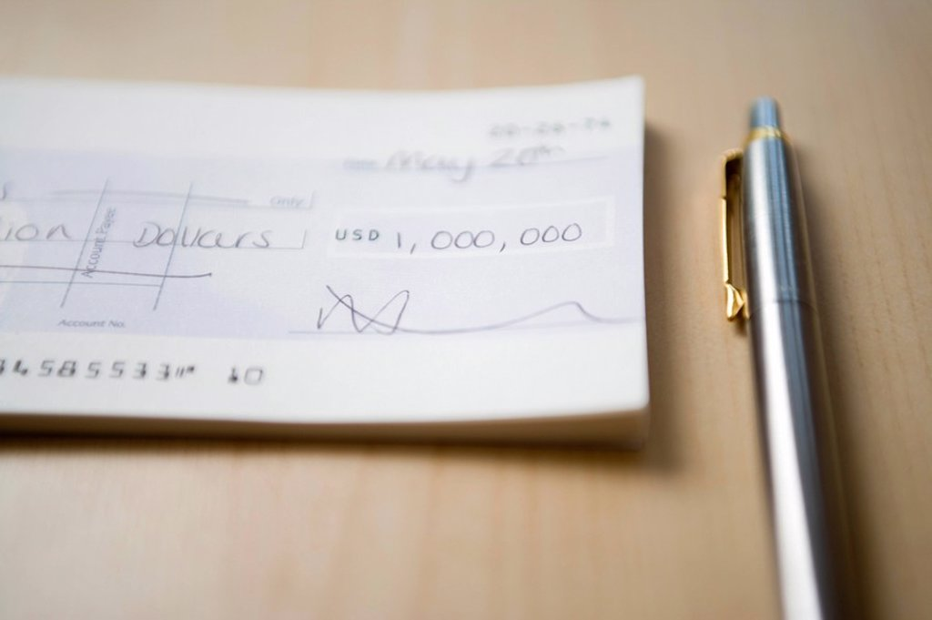 Stock Photo: 1654R-7057 Cheque for one million dollars lying next to pen on table close_up